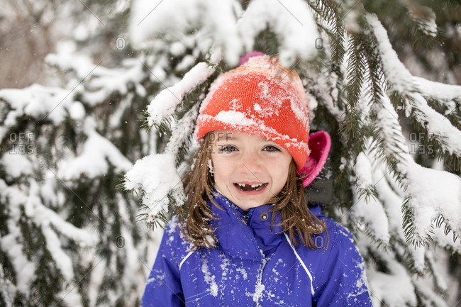 Portrait of cheerful girl wearing warm clothing while standing against snow covered tree