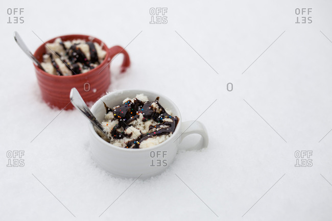 Close-up of dessert with spoons in cups on snow
