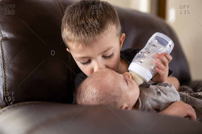 Boy feeding milk to brother from baby bottle while kissing him at home