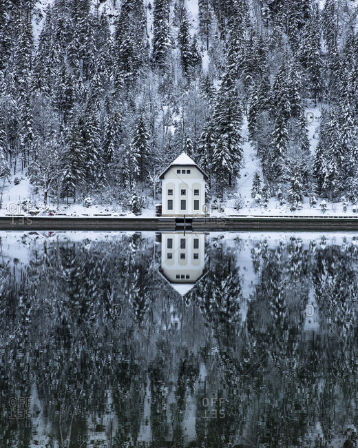 Austria, Tirol, Plansee - February 5, 2018: House and snow covered trees reflecting on calm lake