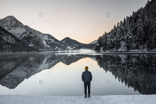 Rear view of man standing at lakeshore against sky during winter
