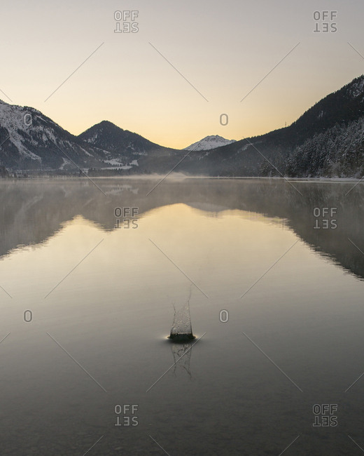 Rippled lake by mountains against sky during sunset