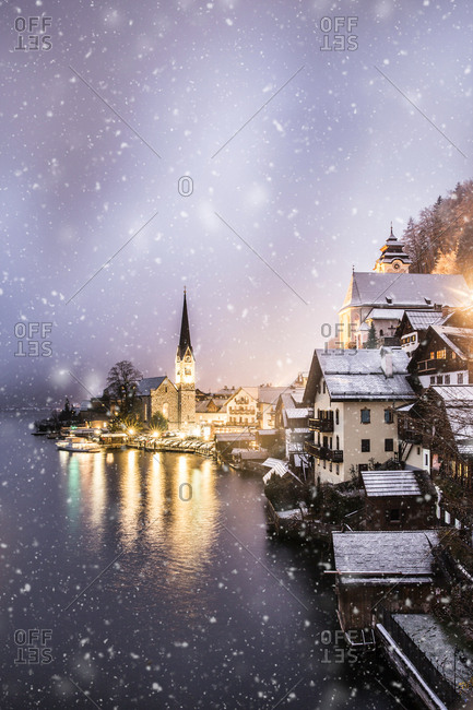 Austria, Hallstatt - December 8, 2017: Illuminated buildings by lake against sky during snowfall at sunset