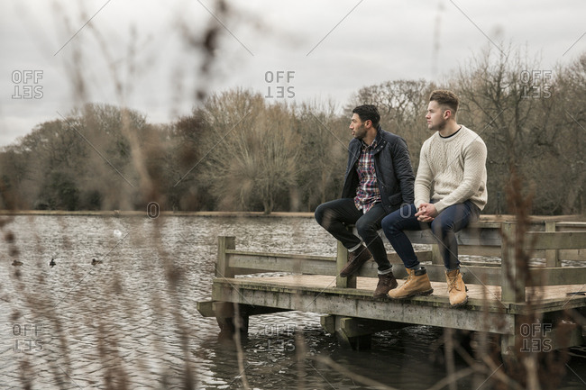 Friends looking away while sitting on pier over lake in Epping Forest