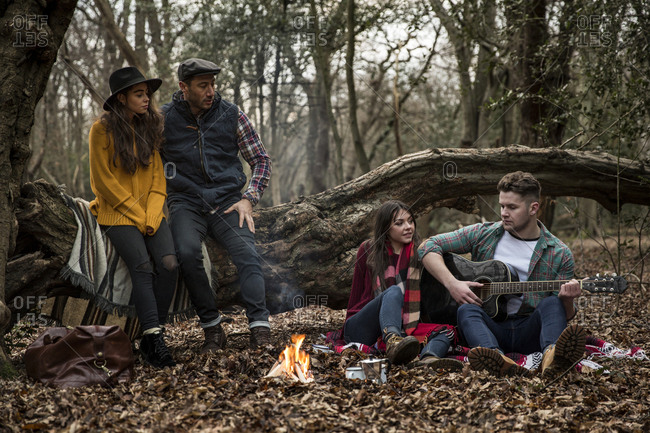 Man playing guitar while sitting with friends in Epping Forest