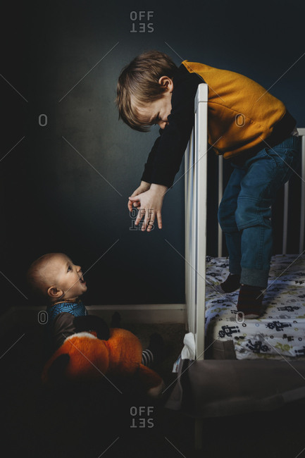 Boy gesturing to brother while standing in crib at home