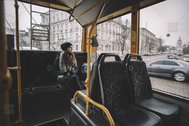Thoughtful woman looking through window while traveling in trolley bus