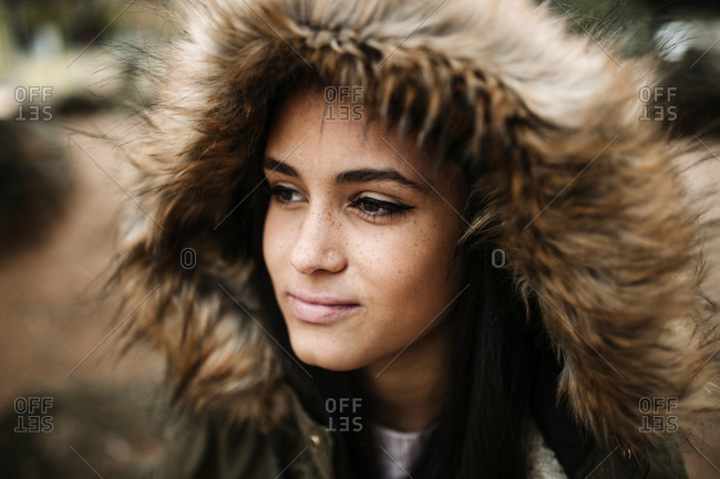 Close-up of thoughtful teenage girl in winter coat looking away while standing outdoors