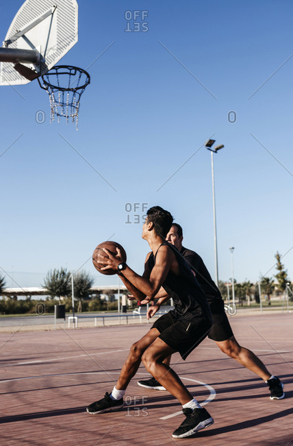 Basketball player and coach practicing at court