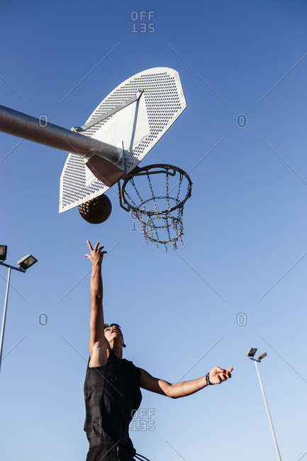 Low angle view of teenage boy throwing ball into basketball hoop against clear sky