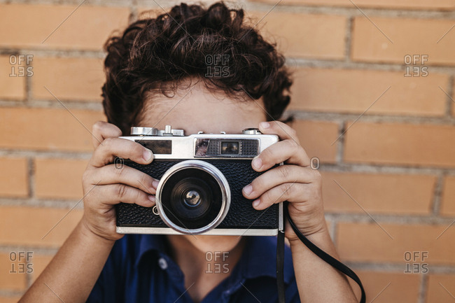 Close-up of boy photographing with vintage camera against brick wall