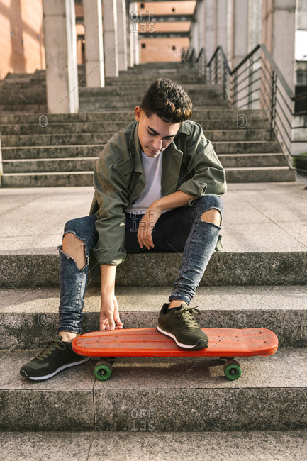 Full length of young man with skateboard sitting on steps
