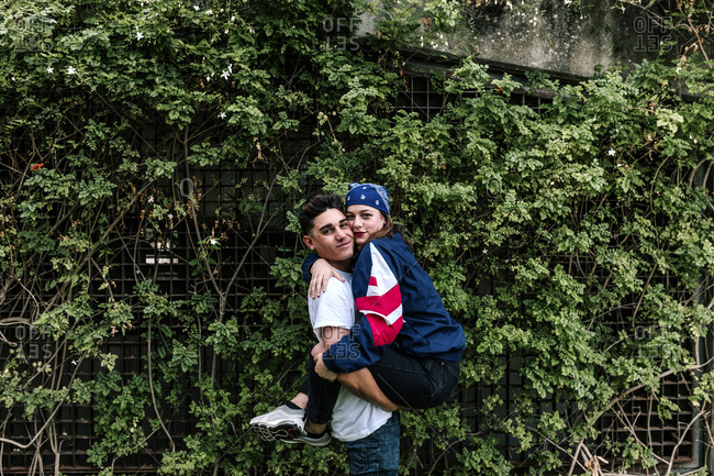 Portrait of boyfriend carrying girlfriend against plants at park