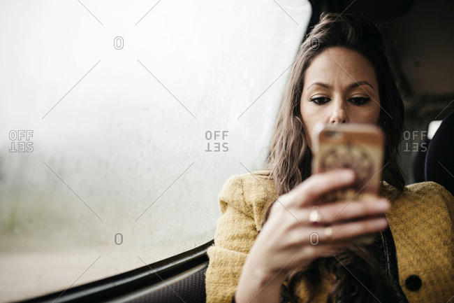 Woman using mobile phone while traveling in car