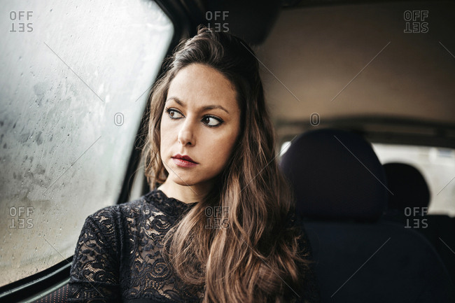Thoughtful woman looking through window while traveling in car