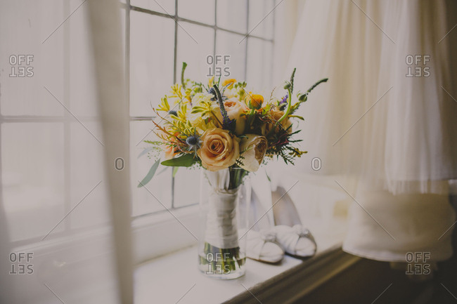 Flower vase and shoes on window sill by wedding dress