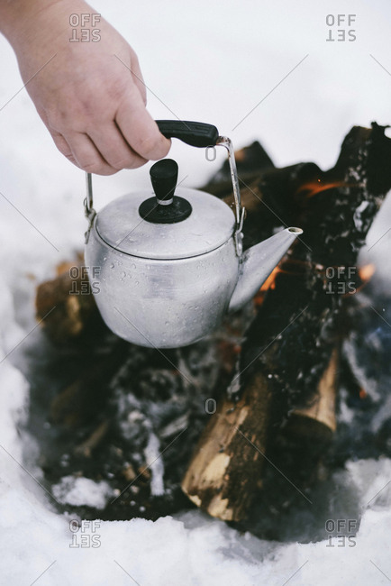 Cropped hand holding kettle over campfire during winter