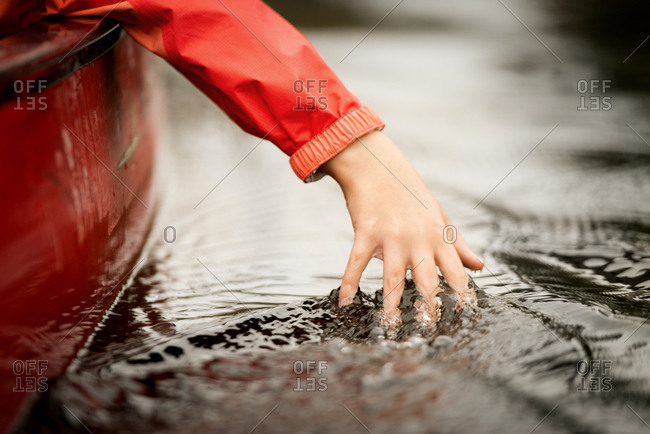 Cropped hand of girl touching water while traveling in boat on river