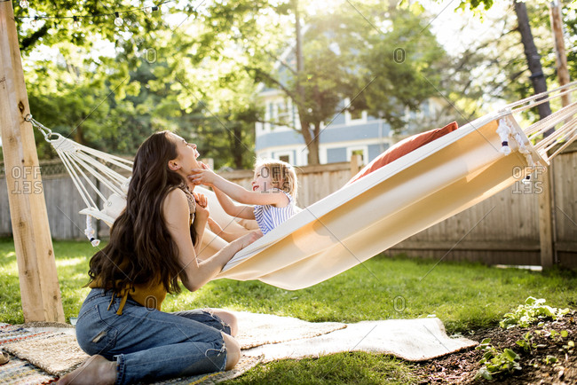Happy mother playing with daughter sitting in hammock at yard