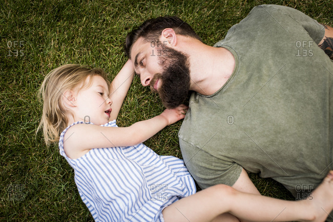 High angle view of father with daughter lying on grassy field at yard
