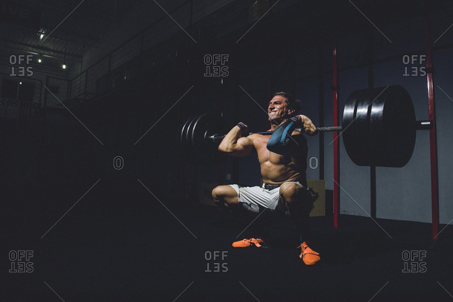 Full length of shirtless man lifting dumbbell in darkroom at gym