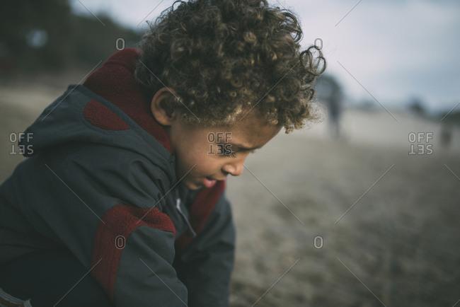 Boy wearing jacket while playing at beach