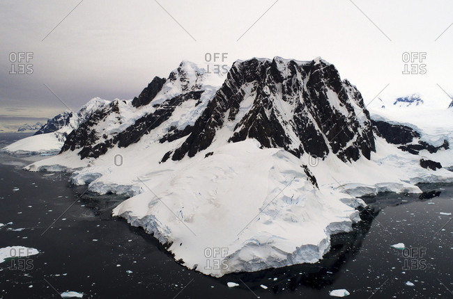 High angle view of snow covered mountain in sea against cloudy sky
