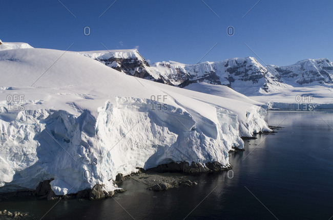 Scenic view of snow covered mountains by sea against clear blue sky