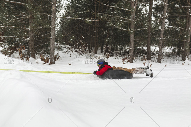 Teenage boy being towed with inflatable ring on snow covered field in forest
