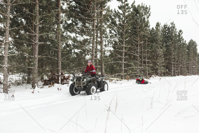 Brother towing sister with inflatable ring while driving quad bike on snow covered field