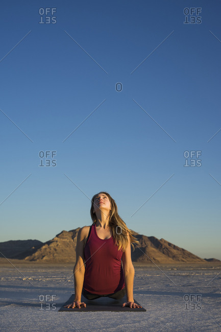 Woman practicing upward facing dog position against clear blue sky during sunset