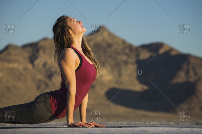 Side view of woman practicing upward facing dog position against clear blue sky during sunset