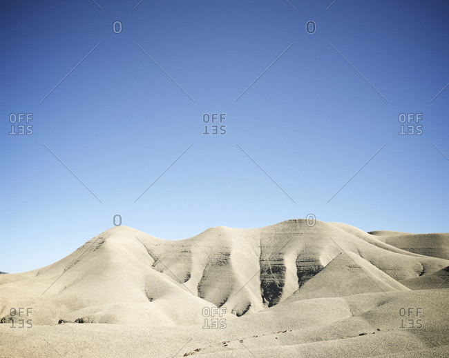 Scenic view of desert against clear blue sky during sunny day