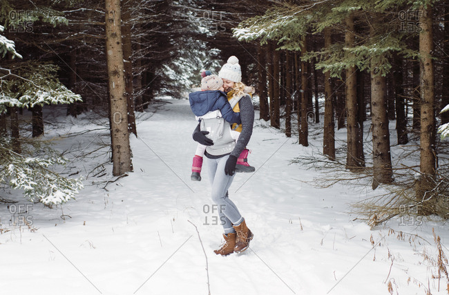 Happy mother carrying daughter while standing in forest during winter
