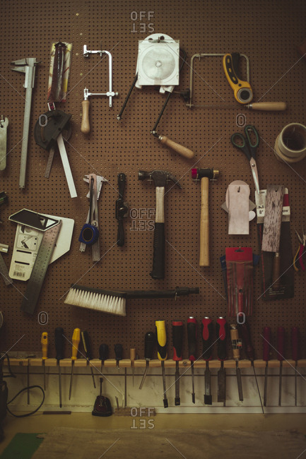 Hand tools hanging on pegboard at guitar workshop