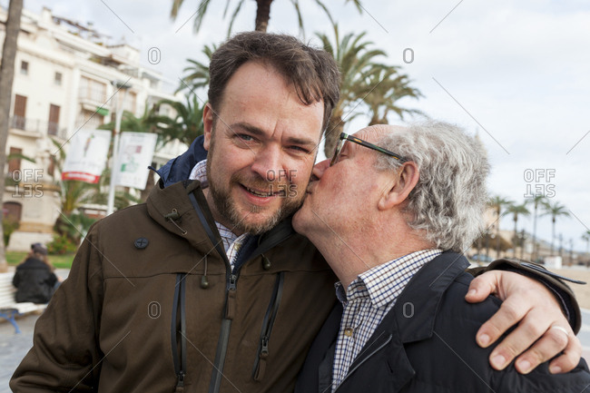 Portrait of son with loving father kissing him in city