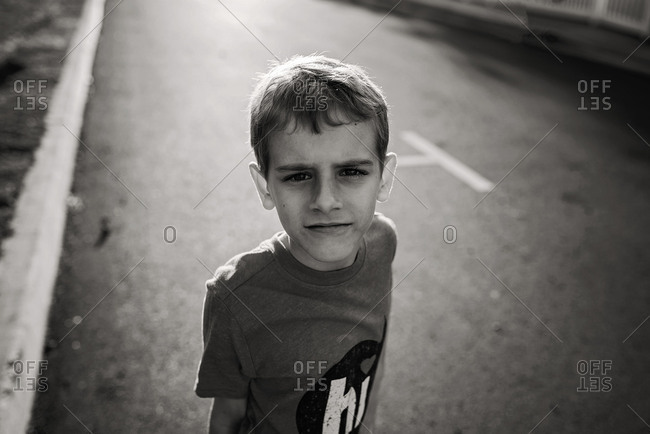 Portrait of boy standing in street in black and white