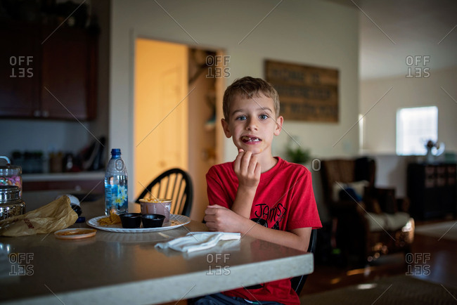 Boy sitting at kitchen counter eating lunch