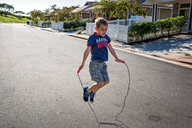 Young boy jumping rope in the street