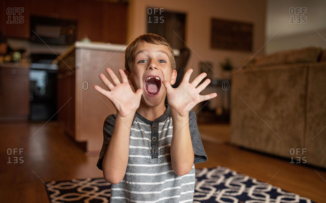 Young boy missing two front teeth holding his hands in the air
