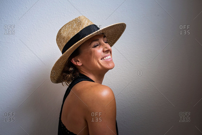 Woman wearing hat smiling with her eyes closed
