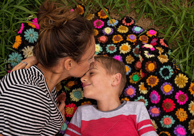 Mother kissing son's forehead while lying on blanket outdoors