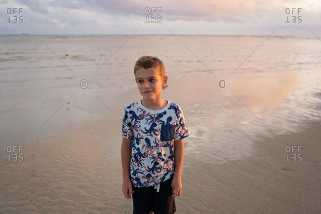 Boy standing on a beach at sunset