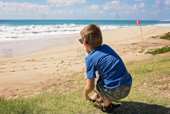 Rear view of boy looking out at waves on a beach
