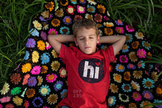 Little boy relaxing on a colorful blanket outdoors