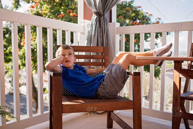 Boy relaxing on wooden chair on a balcony