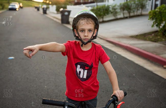 Young boy with bike in the street pointing