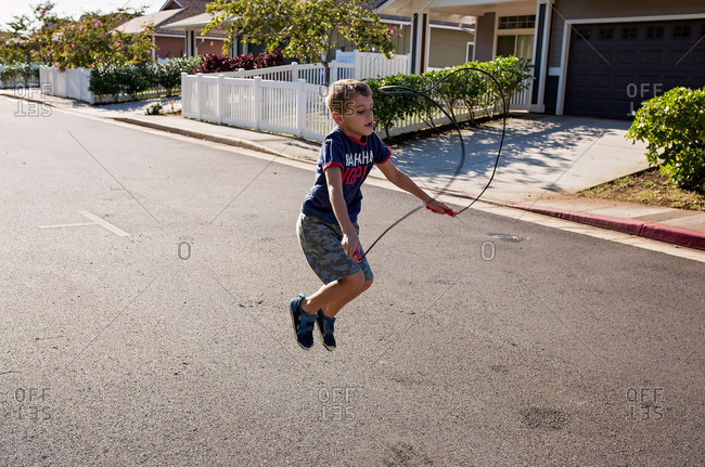 Young boy with a jump rope in the street