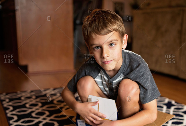 Portrait of a young boy sitting in a cardboard box