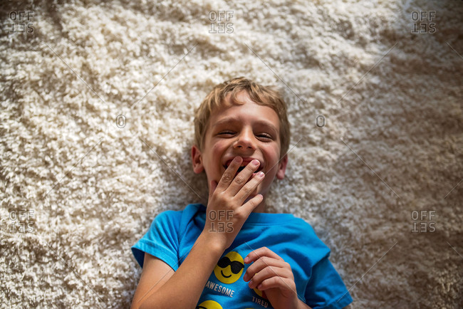 Boy lying on carpet covering mouth while laughing